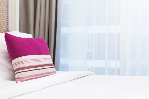 Pink stripe pillow on white bed in a brighly lit bedroom