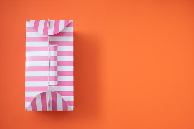 Розовая полосатая подарочная коробка на оранжевом фоне