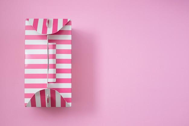 Розовая полосатая подарочная коробка на розовом фоне