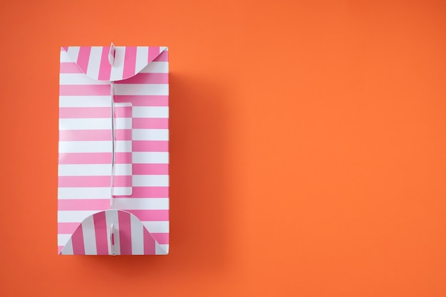Pink striped gift box on orange background