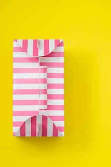 Pink striped gift box on yellow background