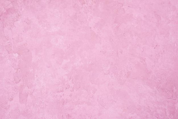 ピンクの漆喰壁の背景。ピンクの塗られたセメントの壁の質感