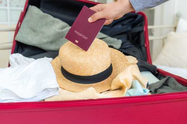 Pink suitcase on the bed with clothes, summer hat and passport in the hand, ready for travel.