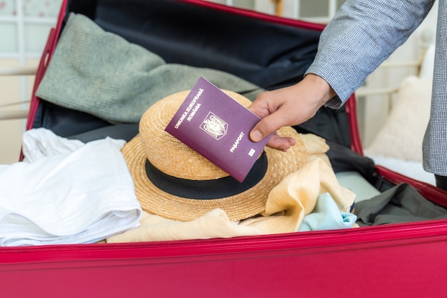 Pink suitcase on the bed with clothes summer hat and romanian passport in hand ready for travel