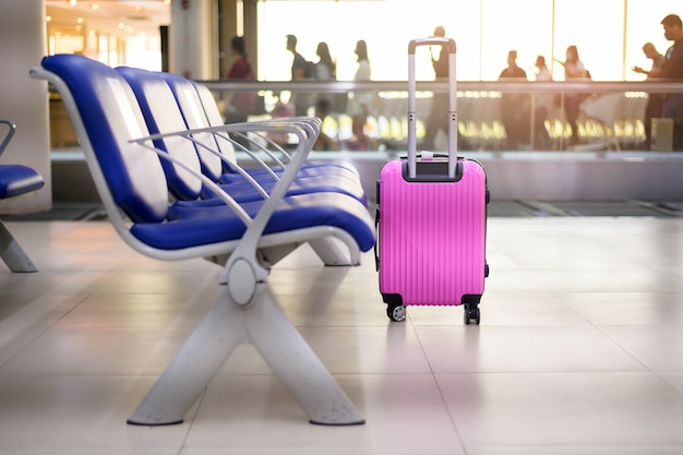 A pink suitcase in departure terminal at the airport