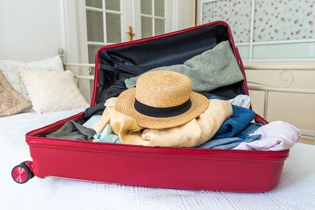 Розовый чемодан на кровати с одеждой, летней шапкой и паспортом, готов к путешествию.