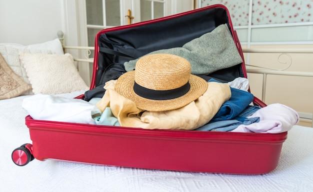 Розовый чемодан на кровати с одеждой, летней шляпой и паспортом, готовый к путешествию.
