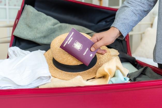 Розовый чемодан на кровати с одеждой, летняя шапка и румынский паспорт в руке, готовый к путешествию
