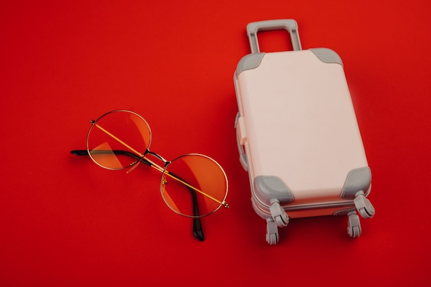 바퀴와 노란색 선글라스에 핑크 가방. 여행 및 휴가 개념