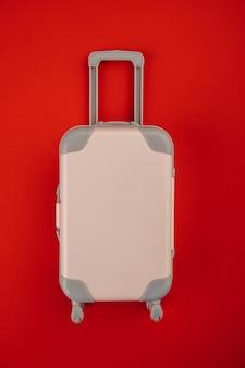 빨간색 배경 여행 컨셉에 바퀴에 핑크 가방