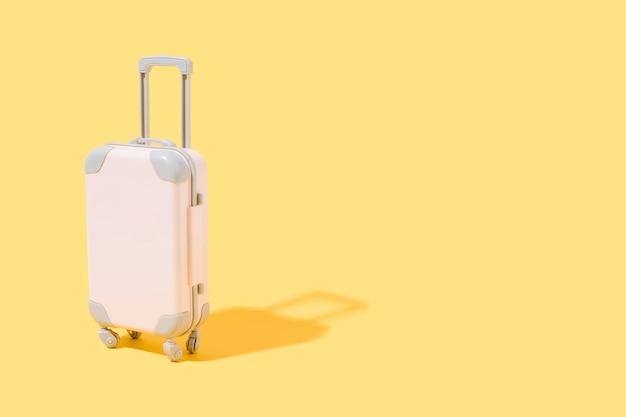 Розовый чемодан на желтом фоне концепции путешествий и летней 3d иллюстрации копией пространства