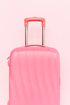 Pink suitcase for travelling against pink background