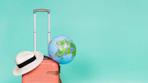 Pink suitcase with hat and globe on it