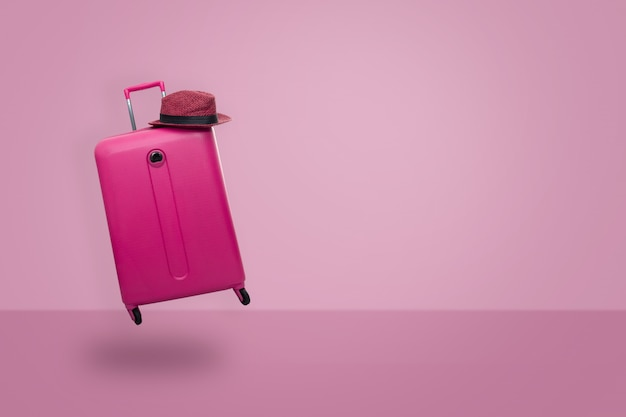 Pink suitcase with hat on pastel pink background. travel concept.