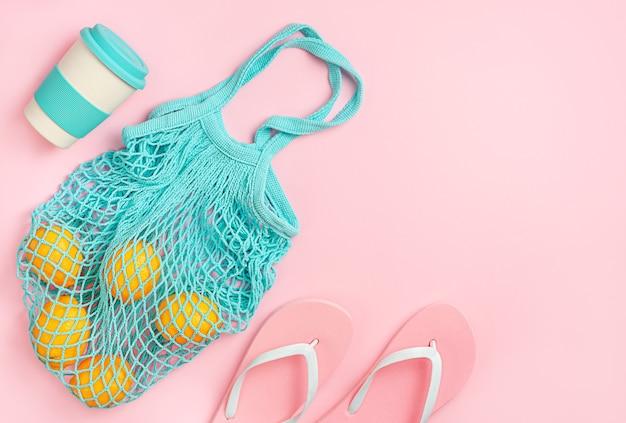Розовый летний фон с шлепками, многоразовой сумкой и эко-чашкой. прямо вверху скопируйте пробел.