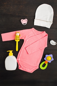 Розовое летнее боди, шапка, два силиконовых пустышки и две деревянные и пластиковые погремушки на коричневом деревянном столе