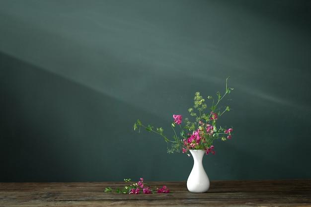 暗い背景に木製のテーブルの上のピンクの夏の花