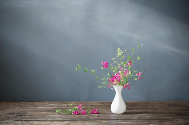暗い背景の上の木製のテーブルの上のピンクの夏の花