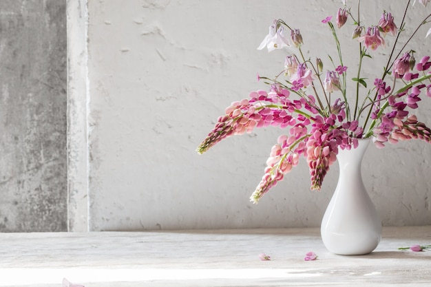 Pink summer flowers in white vase on white old background