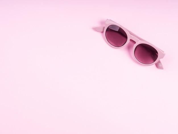 Pink sun glasses on monochrome backdrop