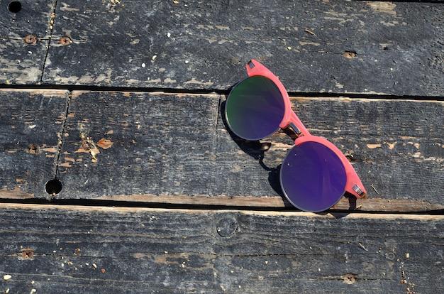 Розовые солнцезащитные очки против солнца на деревянном фоне у моря