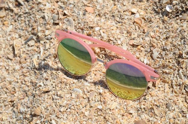 ビーチの砂の上で太陽に対してピンクのサングラス