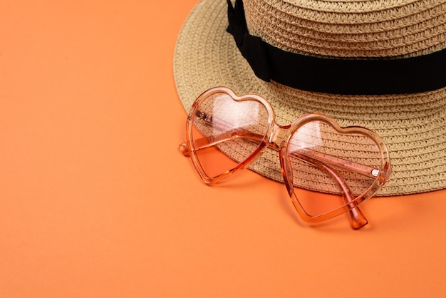 Розовые солнцезащитные очки и шляпа на оранжевом фоне. скопируйте пространство.