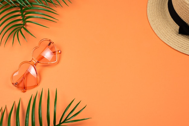 Розовые солнцезащитные очки и шляпа на оранжевом фоне