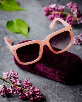 Pink sunglasses around beatiful flowers on the grey surface