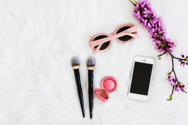 Pink sunglasses; purple flower twig; compact face powder; makeup brushes and mobile phone on fur backdrop