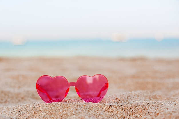 Pink sunglasses on a sandy beach with a blue sea background, honeymoon, vacation, copy space