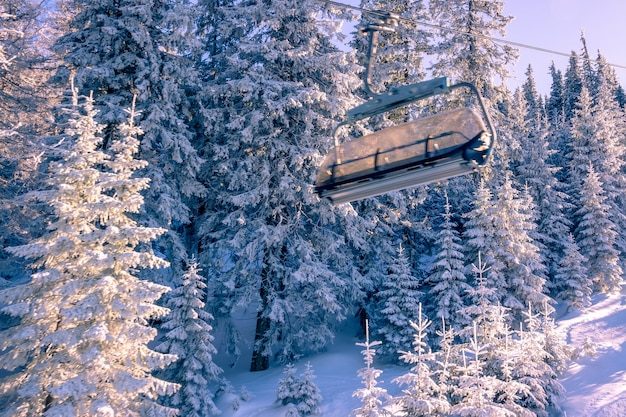 Pink sunny morning in the winter forest. a lot of snow on the tree branches. empty cabin of a ski chair lift
