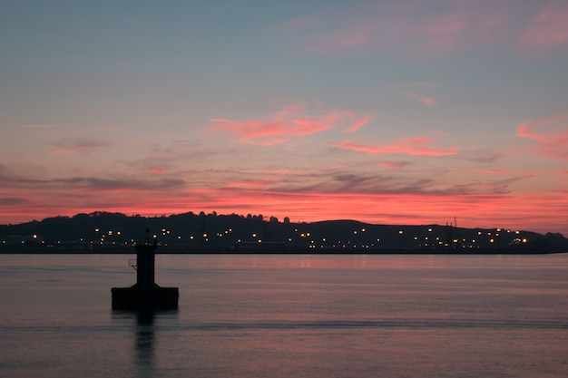 Pink sunset a lake and city lights