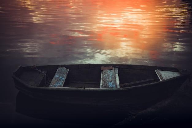 古いボートと湖のピンクの夕日。ぼやけた自然の背景、湖に沈む夕日。シルエットネイチャーバナー