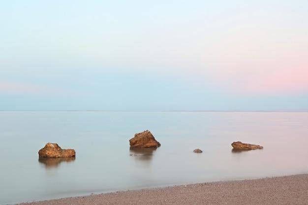 잔잔한 바다 위의 핑크색 일몰 전경의 돌과 긴 노출이 있는 바다의 나무 돌