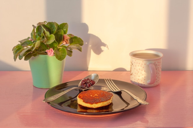 On the pink surface there is a black plate with a pancake, next to it is a fork and a spoon with jam. next to it is a cup of tea and a violet in a pot. breakfast concept and good morning.