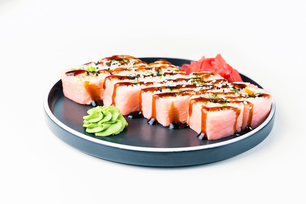 Pink sushi roll in black plate on white background. japanese food.