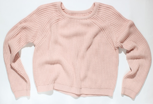 Pink sweater on white, top view