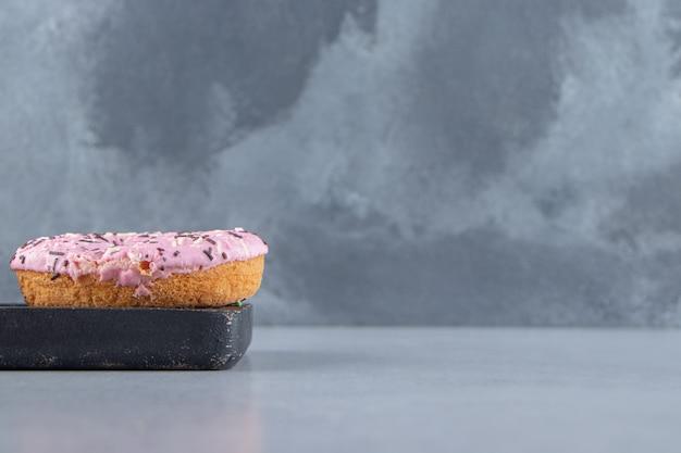 Ciambella dolce rosa decorata con granelli sul tagliere. foto di alta qualità