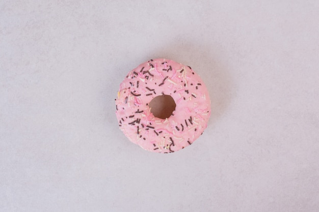 Розовый сладкий пончик на белой поверхности