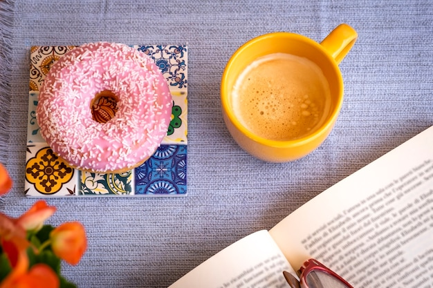 Pink and sweet glazed donut on the table, a break with a book and a cup of coffee