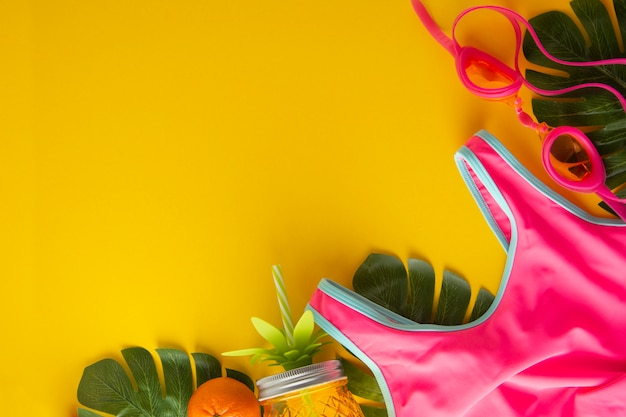 Pink swimming suit and pineapple jar for juice. summer background with copy space.