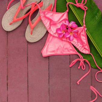 Pink swimsuit frangipani palm leaf swimming pool