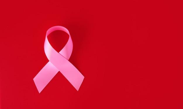 Розовая лента символа на красной поверхности