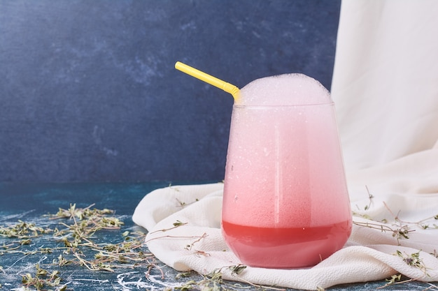 Sciroppo rosa con una tazza di bevanda sull'azzurro.