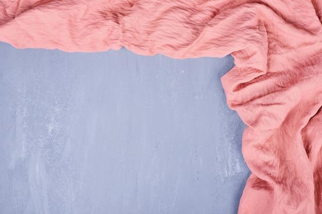 青いテーブルの上のピンクのテーブルクロスのフレーミング。