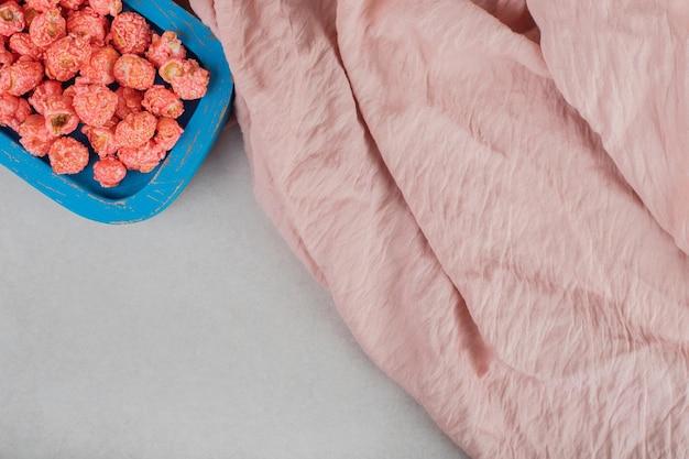 大理石のテーブルの上のポップコーンキャンディーの小さな木製の大皿の横にあるピンクのテーブルクロス。