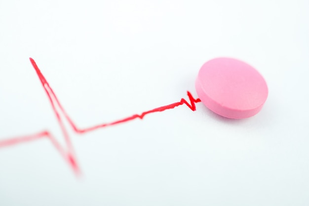 Pink tablet with the chart of red color. concept of medicine for the heart.