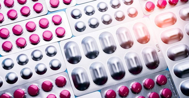 Pink tablets in blister pack and silver aluminium foil pack for capsule and tablets pills in pharmaceutical industry.