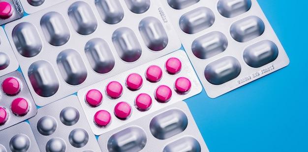 Розовые таблетки в блистерной упаковке и упаковке из алюминиевой фольги для капсул и таблеток пилюль